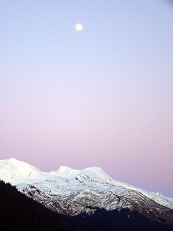 beautiful image of the moon rising over the mountains in southeast alaska